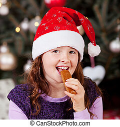Little girl eating Christmas candy - Little girl wearing a...