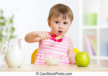 Little girl eating cornflakes with milk in home