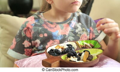 Little girl eating dried fruit