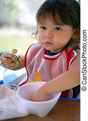 Little girl eating grapes from a bowl