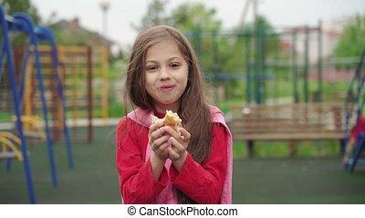Little girl eating hamburger on children playground. Summer ...