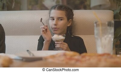 little girl eating ice cream at a fast food cafe slow motion...