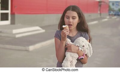 little girl eating ice cream goes down the street with a...