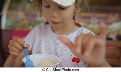 Little girl eating ice cream in street cafe