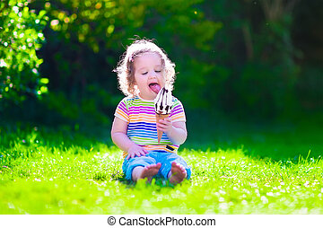 Little girl eating ice cream in the garden - Child eating...