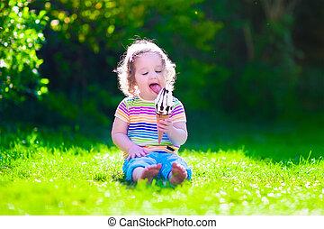 Little girl eating ice cream in the garden - Child eating...