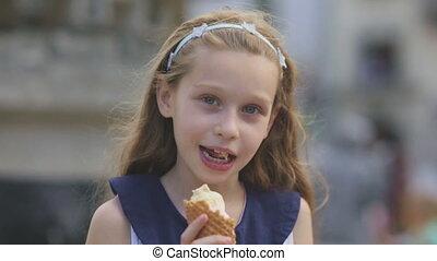 Little girl eating Ice Cream on a Hot, Torrid Summer Day at Playground in Park, Children