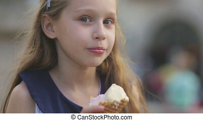 Little girl eating Ice Cream on a Hot, Torrid Summer Day at Playground in Park, Children