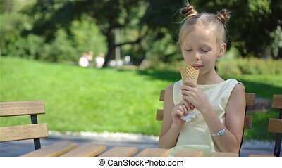 Little girl eating ice-cream outdoors at summer in outdoor cafe