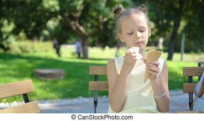 Little girl eating ice-cream outdoors at summer in outdoor cafe. Cute kid enjoying real italian gelato