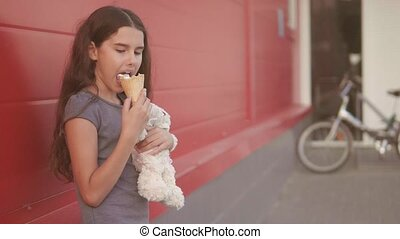 little girl eating ice cream the street with a soft toy...