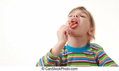 little girl eating lollipop in chicken form
