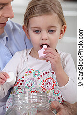 Little girl eating marshmallows with her dad