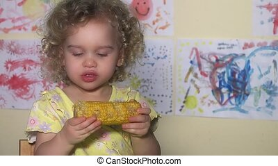 little girl eating messy corn on the cob. Static closeup...