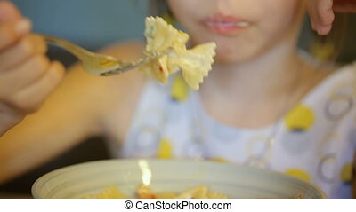 Little girl eating pasta in cafe