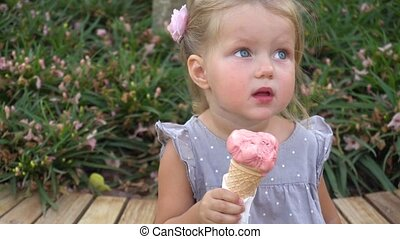 Little girl eating pink ice cream in the park - Adorable...