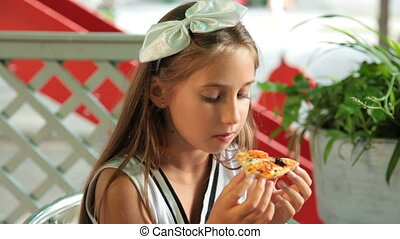 Little girl eating pizza at outdoor cafe