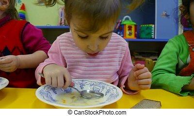 Little girl eating porridge in the kindergarten