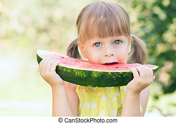 Little girl eating ripe watermelon in sunny summer garden