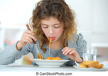 Little girl eating spaghetti at home