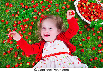 Little girl eating strawberry - Child eating strawberry....