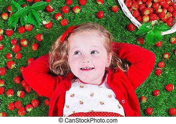 Little girl eating strawberry - Child eating strawberry....
