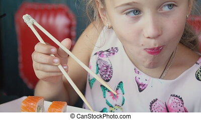little girl eating sushi sitting at the table
