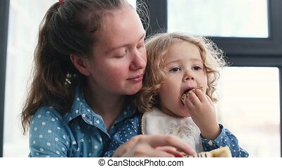 Little girl eating sweet cake sitting at mom lap. The mother...
