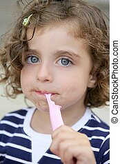 Little girl eating sweet candy with dirty face
