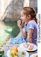Little girl eating sweets - Adorable little girl enjoying...