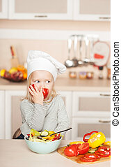Little girl eating tomato while cooking salad in kitchen