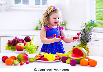 Cute curly little girl in a colorful summer dress eating fresh tropical fruit and berry for healthy breakfast snack in a white sunny family kitchen