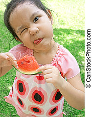 Little girl eating watermelon in summer time;