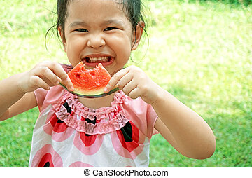 Little girl eating watermelon in summer time
