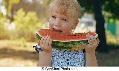Little girl eating watermelon on nature