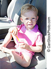 little girl eating yogurt in the car