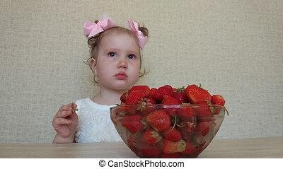 little girl eats a ripe strawberry