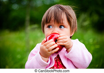 little girl eats an apple