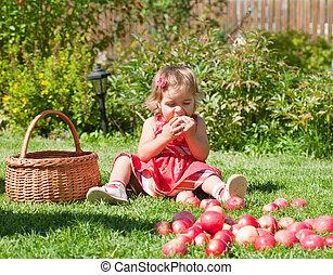 little girl eats an apple, sitting on a grass