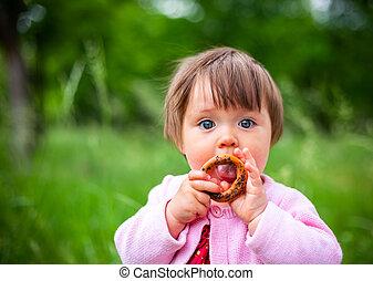 little girl eats bagel