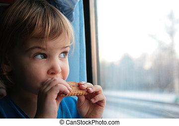 little girl eats cookies end looks in train`s window