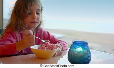 Little girl eats ice cream and watch on candle with seascape behind