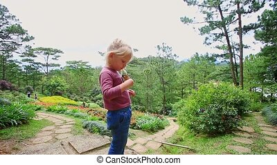 Little Girl Eats Ice Cream on Rocky Path in Park