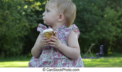 little girl eats ice cream with appetite and licks fingers