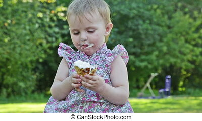 little girl eats ice cream with appetite, sitting in park on...