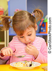 Little girl eats in kindergarten