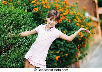 Little girl, eight years old, having fun in an urban park.