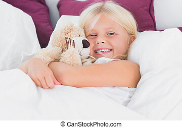 Little girl embracing her cuddly toy on the bed