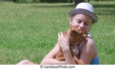 Little girl embracing her puppy dog in summer park