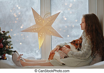 Little girl embracing her puppy dog sitting on window s and waiting Christmas.